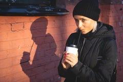 Mujer alegre en el café de consumición de la mañana de la calle en invierno foto de archivo