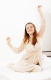 Mujer alegre en el nightrobe que se despierta en cama en casa Imágenes de archivo libres de regalías