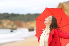 Mujer alegre en el rojo emocionado con el paraguas Fotos de archivo libres de regalías