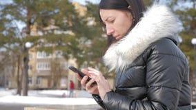 Mujer alegre en el teléfono en un parque de la ciudad que se sienta en un banco almacen de video