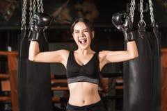 Mujer alegre en guantes de boxeo que celebra la victoria Imagenes de archivo