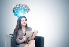Mujer alegre en la butaca, una tableta, cerebro Fotos de archivo