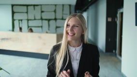 Mujer alegre en la oficina que agita con la mano Mujer joven elegante en la chaqueta que agita con la mano al saludo anónimo de l metrajes