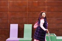 Mujer alegre en un vestido rosado y un cabo púrpura de la piel que montan una vespa imagen de archivo