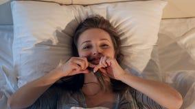 Mujer alegre, feliz que hace caras en cama 4K almacen de video