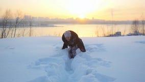 Mujer alegre feliz que se divierte al aire libre que lanza nieve a la cámara en naturaleza nevosa del invierno en la cámara lenta metrajes