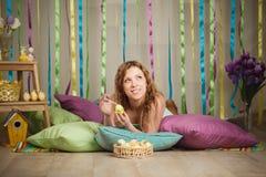 Mujer alegre hermosa en el interior colorido de pascua Foto de archivo libre de regalías