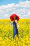 Mujer alegre hermosa en un sombrero rojo con un ramo en manos imagenes de archivo