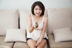 Mujer alegre hermosa joven que sostiene el telecontrol Imagen de archivo
