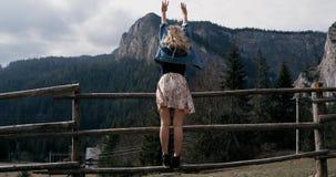 Mujer alegre joven que aumenta sus brazos en el top hermoso de la montaña sobre el cielo de oro de la puesta del sol 4K almacen de video