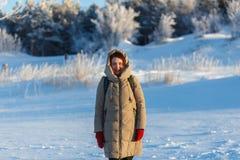 Mujer alegre joven que camina en el día soleado frío del invierno en el fondo de árboles y de la nieve Muchacha vestida en calien Imágenes de archivo libres de regalías