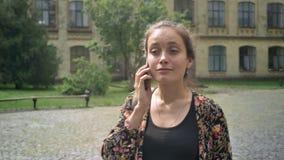 Mujer alegre joven que camina en la calle cerca de universidad y que habla en el teléfono, estudiante universitario de sexo femen almacen de video