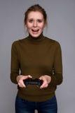 Mujer alegre joven que juega a los videojuegos Imágenes de archivo libres de regalías