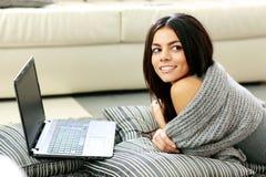 Mujer alegre joven que miente con el ordenador portátil y que mira lejos Imagenes de archivo
