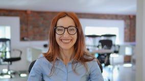 Mujer alegre joven que presenta en el trabajo almacen de video