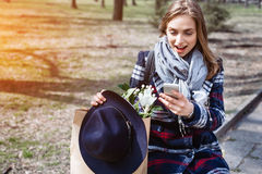 Mujer alegre joven que presenta mientras que se fotografía en la cámara elegante del teléfono para una charla con los amigos, atr Imagenes de archivo