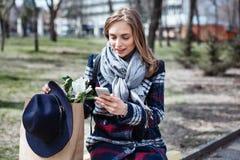 Mujer alegre joven que presenta mientras que se fotografía en la cámara elegante del teléfono para una charla con los amigos, atr Imagen de archivo