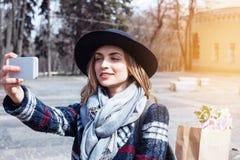 Mujer alegre joven que presenta mientras que se fotografía en la cámara elegante del teléfono para una charla con los amigos, inc Foto de archivo libre de regalías