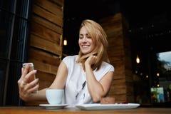 Mujer alegre joven que presenta mientras que se fotografía en la cámara elegante del teléfono para una charla con sus amigos, Foto de archivo