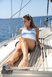 Mujer alegre joven que se relaja en cruzar del barco de navegación Imagenes de archivo
