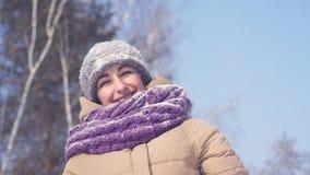 Mujer alegre joven que sopla en la nieve en las palmas metrajes