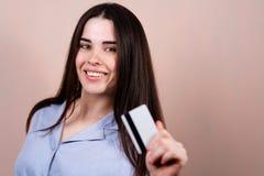 Mujer alegre joven que sostiene la tarjeta de crédito fotografía de archivo