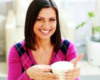 Mujer alegre joven que sostiene la taza de café Fotografía de archivo libre de regalías