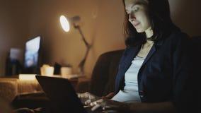 Mujer alegre joven que trabaja en oficina en la noche usando el ordenador portátil y el mensaje que mecanografía almacen de video