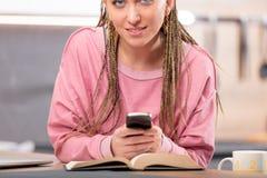 Mujer alegre joven que usa el teléfono móvil en la tabla Imagenes de archivo