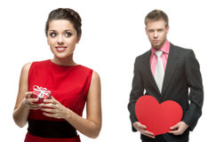 Mujer alegre joven y hombre hermoso que llevan a cabo el corazón rojo en blanco Imagen de archivo