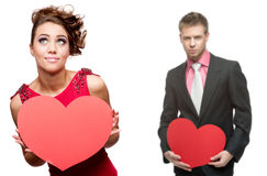Mujer alegre joven y hombre hermoso que llevan a cabo el corazón rojo en blanco Imágenes de archivo libres de regalías