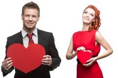 Mujer alegre joven y hombre hermoso que llevan a cabo el corazón rojo en blanco Fotos de archivo libres de regalías