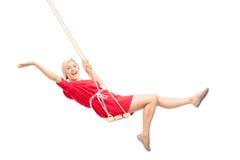 Mujer alegre que balancea en un oscilación Foto de archivo libre de regalías