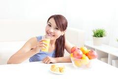 Mujer alegre que bebe un zumo de naranja Foto de archivo libre de regalías