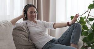 Mujer alegre que canta mientras que música que escucha en los auriculares almacen de metraje de vídeo