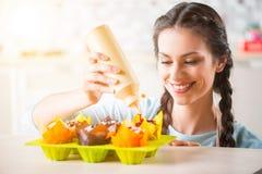 Mujer alegre que cocina las tortas Imágenes de archivo libres de regalías