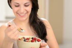 Mujer alegre que come el cereal sano Fotografía de archivo