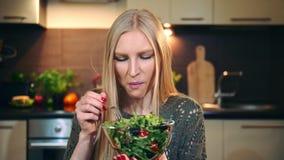Mujer alegre que come la ensalada sana Hembra joven hermosa que goza de la ensalada vegetal sana mientras que se sienta en elegan metrajes