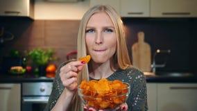 Mujer alegre que come las patatas fritas Hembra joven hermosa que goza de las patatas fritas y que mira la cámara mientras que as metrajes