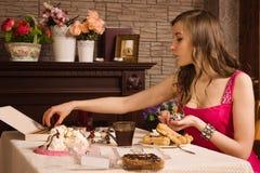 Mujer alegre que come los dulces Foto de archivo