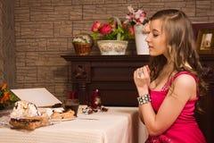 Mujer alegre que come los dulces Fotografía de archivo libre de regalías