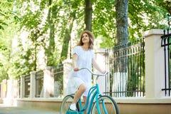 Mujer alegre que completa un ciclo en el parque Foto de archivo