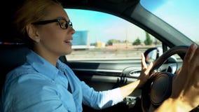 Mujer alegre que conduce y que canta adelante, lleno de energía para el día estimulante imagen de archivo libre de regalías