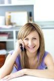 Mujer alegre que contesta al teléfono en la cocina Imágenes de archivo libres de regalías