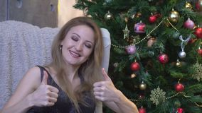 Mujer alegre que da dos pulgares para arriba y que se sienta en fondo del árbol de navidad almacen de video