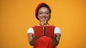 Mujer alegre que estira las manos que muestran en el giftbox rojo de la cámara, presente del día de fiesta metrajes