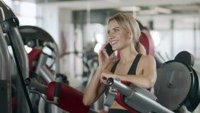 Mujer alegre que habla el teléfono móvil en la máquina del entrenamiento de la aptitud en gimnasio del deporte metrajes