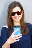 Mujer alegre que habla en el teléfono en el equipo casual de la calle Imágenes de archivo libres de regalías