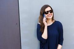 Mujer alegre que habla en el teléfono en el equipo casual de la calle Fotografía de archivo libre de regalías