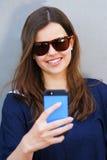 Mujer alegre que habla en el teléfono en el equipo casual de la calle Fotografía de archivo